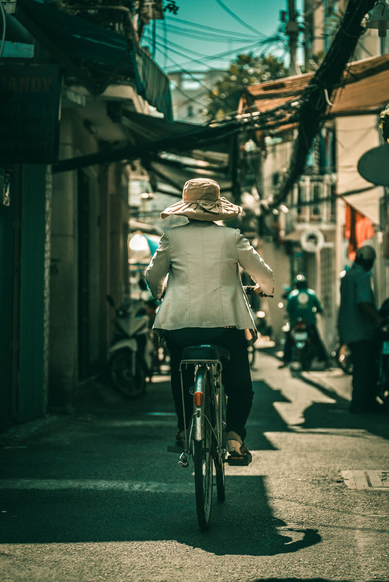 woman riding bicycle in Saigon alley