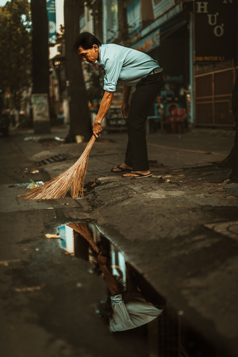 man cleaning street in Vietnam